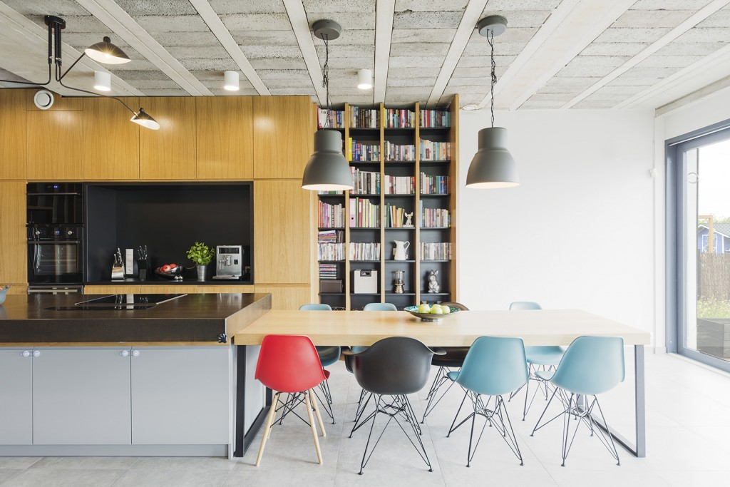 Interior in an industrial style with an open kitchen, dining table and colorful chairs - Shutterstock : 441051442 - Photographee.eu